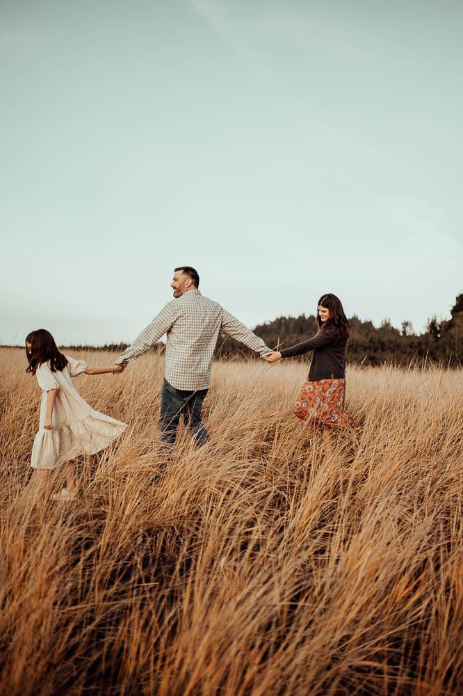 Family of three walking through sea grass